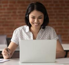 Photo of girl smiling at something on her laptop.