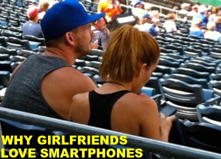 Image of young man and woman at a baseball game. He's watching the game, she's looking at her phone.