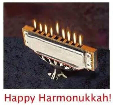 Photo of harmonica on a stand with nine flames coming out of the nine holes and caption: Happy Harmonukkah!