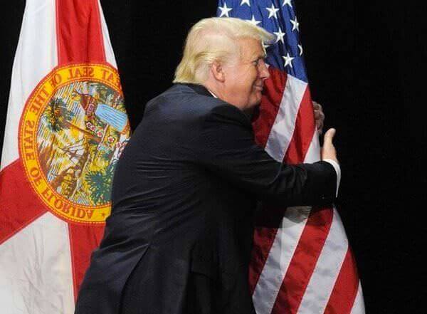 Trump hugging American Flag